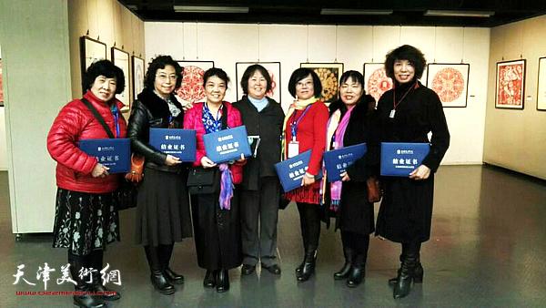 吕爱茹与同学们在天津美术学院全国非物质文化遗产研修研习剪纸班毕业展上。