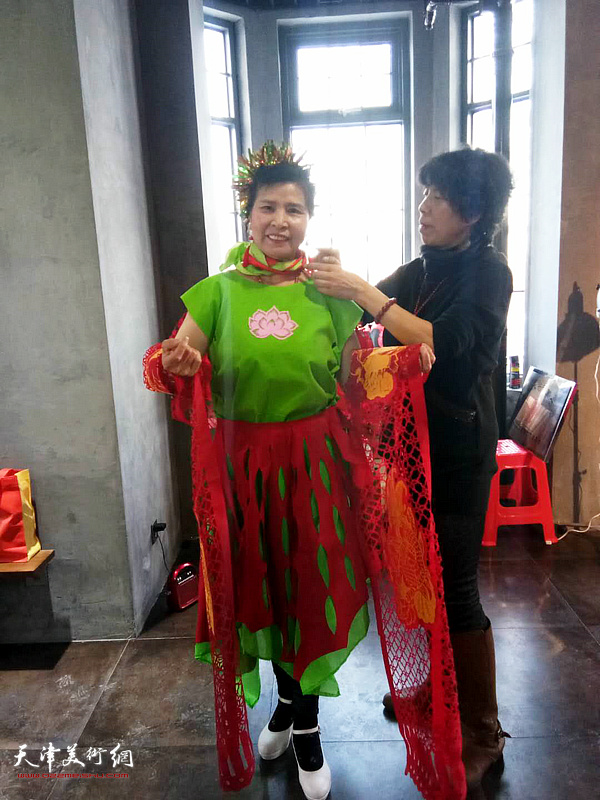 吕爱茹在设计剪纸衣。