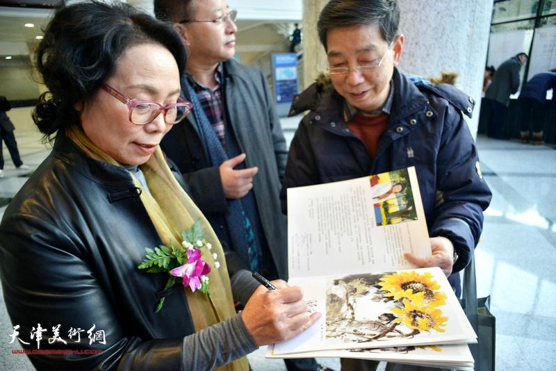 崔燕萍为读者在向日葵画集上签名留念。