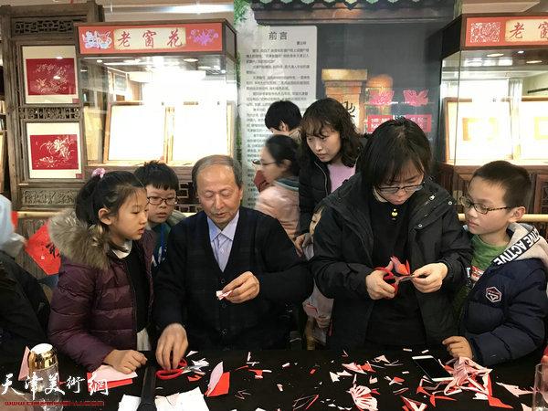 陈汝明老师带孩子们一起动手制作了窗花。
