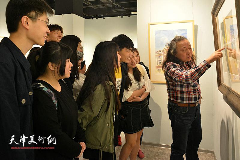 朱志刚在画展现场为大学生们讲解水彩艺术。