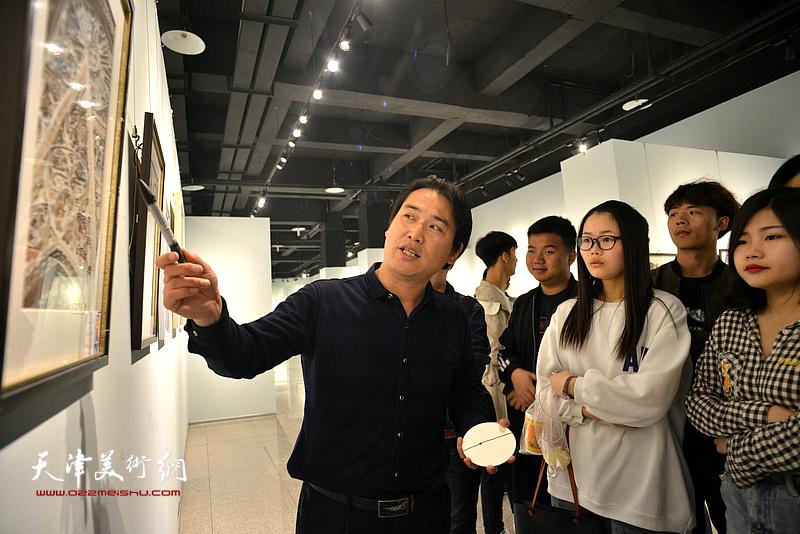滑寒冰在画展现场为大学生们讲解水彩艺术。