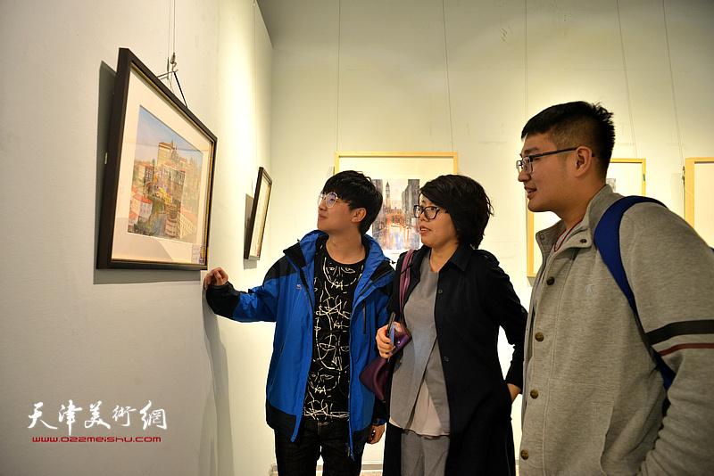 顾素文在画展现场为大学生们讲解水彩艺术。