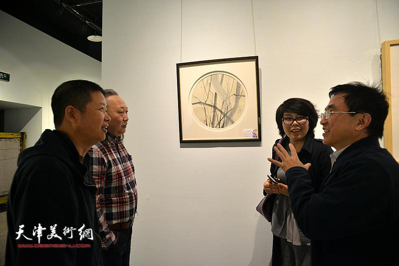 朱志刚、魏瑞江、王文元、顾素文在画展现场交流。