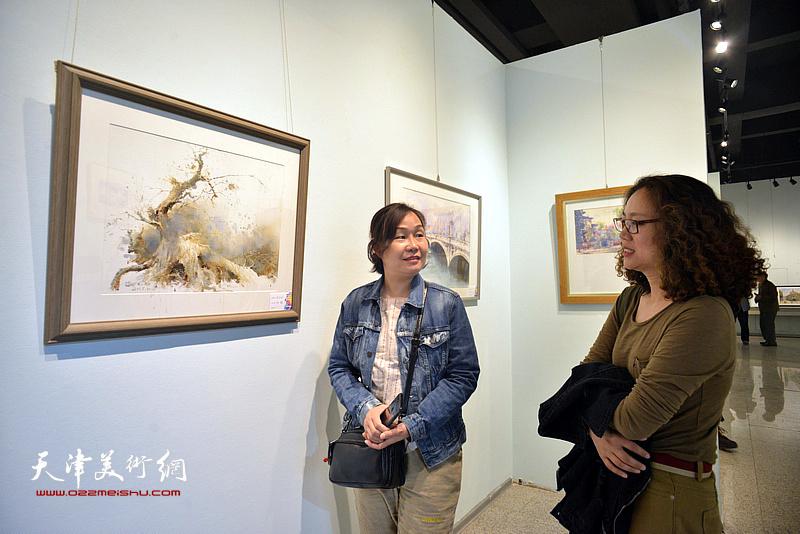 陶香莲、谢红在观赏展出的画作。