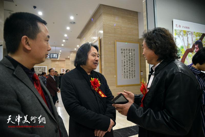 贾广健在画展现场与当地艺术家交流。