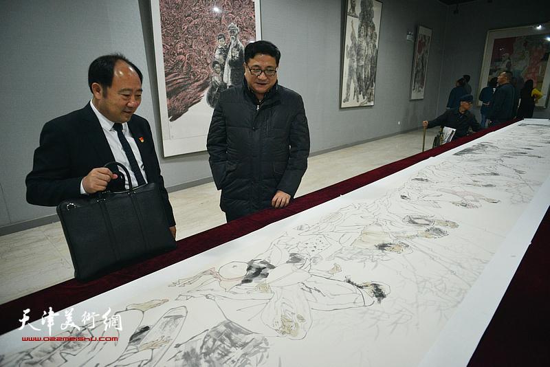 商移山、袁汝海在画展现场观看展品。
