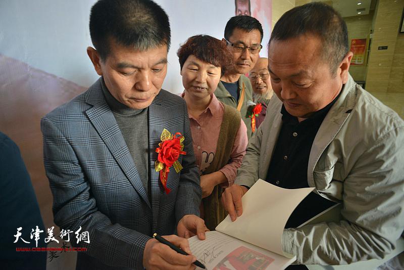 范扬在画展现场为观众在画集上签名。