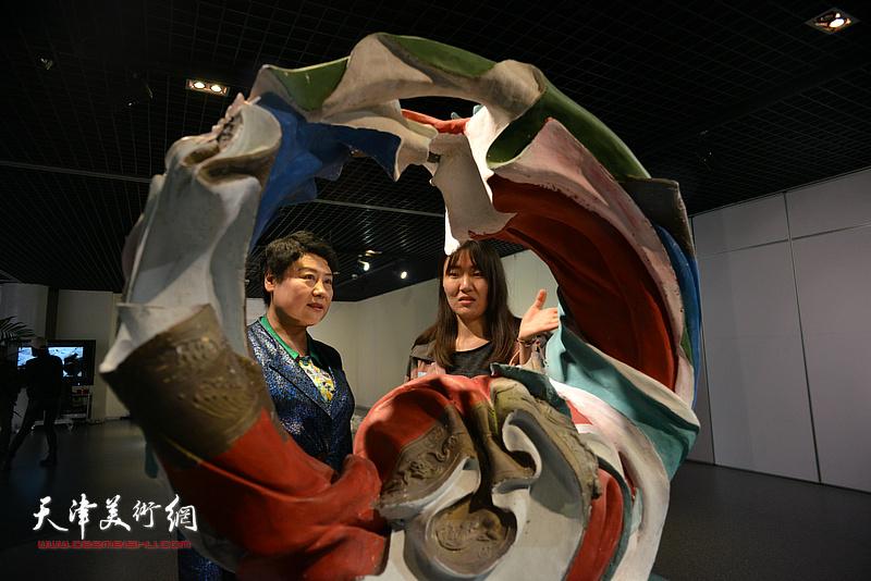 王萍在画展现场观赏张有魁的作品《洗衣店》。