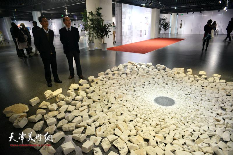 闫红军、朱永年在画展现场观赏田亚的作品《专家计划一生之水》。