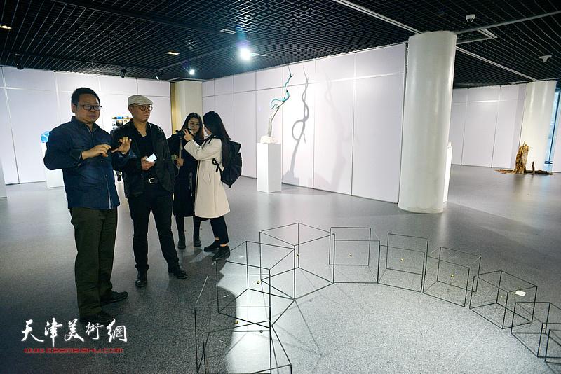 谭勋、黄文智在画展现场观赏郭钰婷的作品《回》。