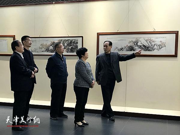 姜金军陪同寿光市各级领导在画展现场观看展品。