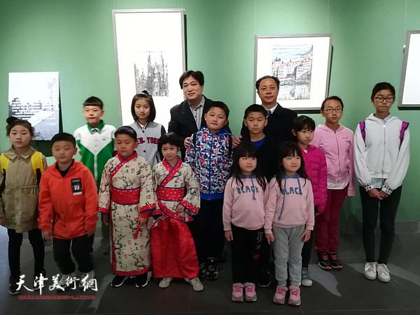 著名画家张大功与各族少年儿童在作品展现场。