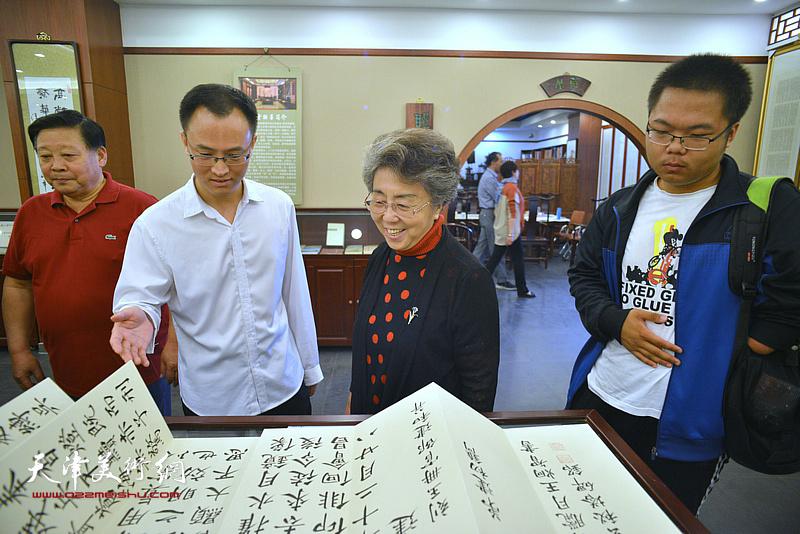 王炯智陪同李润兰、张云友观看展出的作品。