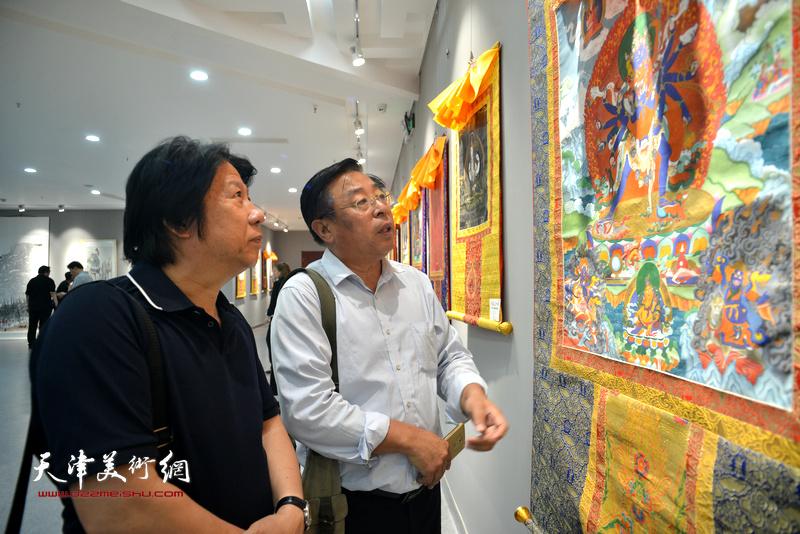 赵俊山、李学亮观赏展出的作品。