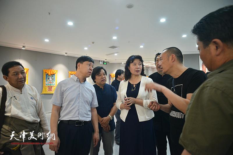 万镜明、张庆岩、李耀春与徐展在画展现场交流。