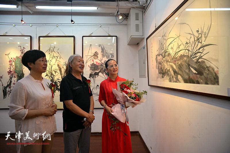 刘家栋、李学萍、李盟观赏展出的画作。
