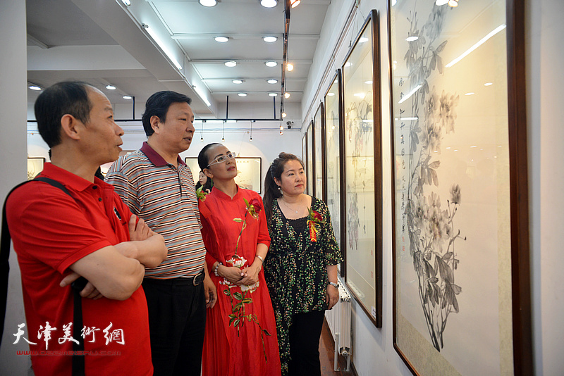 王连宏、启荣、李盟、薛春英观赏展出的画作。