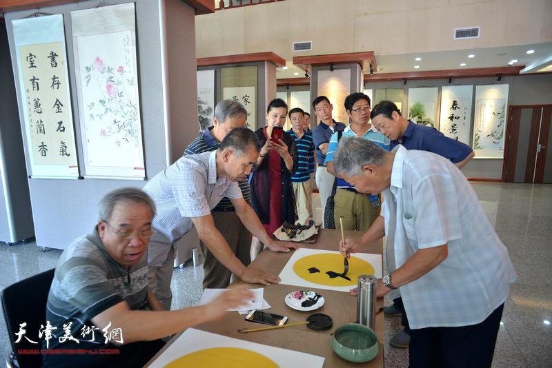 杨柳青镇茹芦书画院书画作品展现场,书画家挥毫创作。