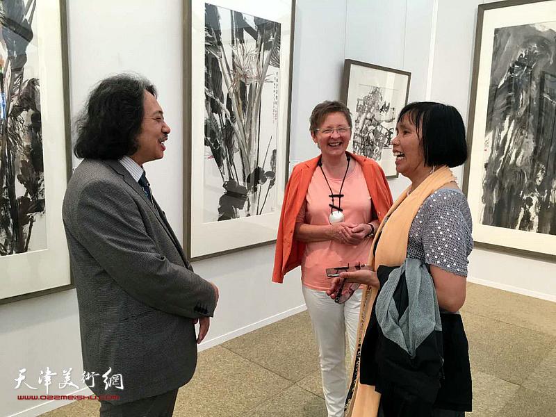 贾广健在展览现场与观众交流。