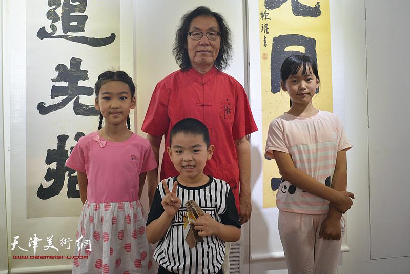 陈栋琨与喜爱书法的小朋友在书法展现场。