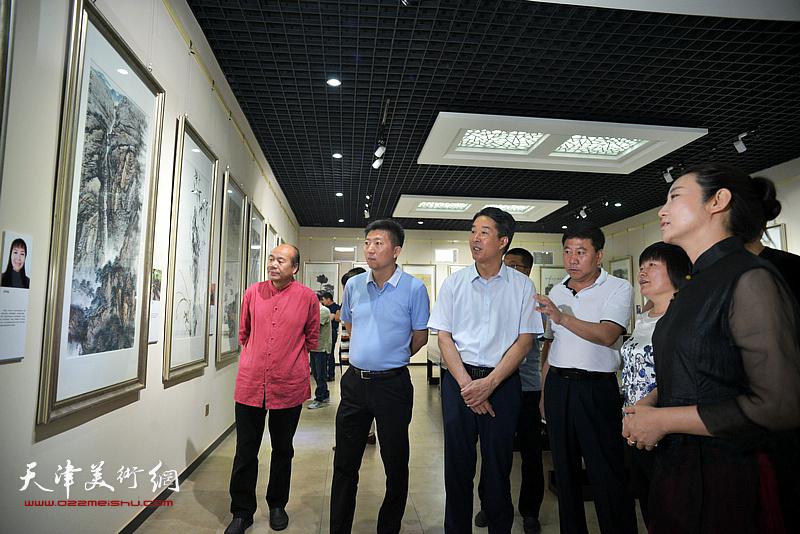 姚新向杨广才、刘亚秀等两区领导介绍展出的画作。