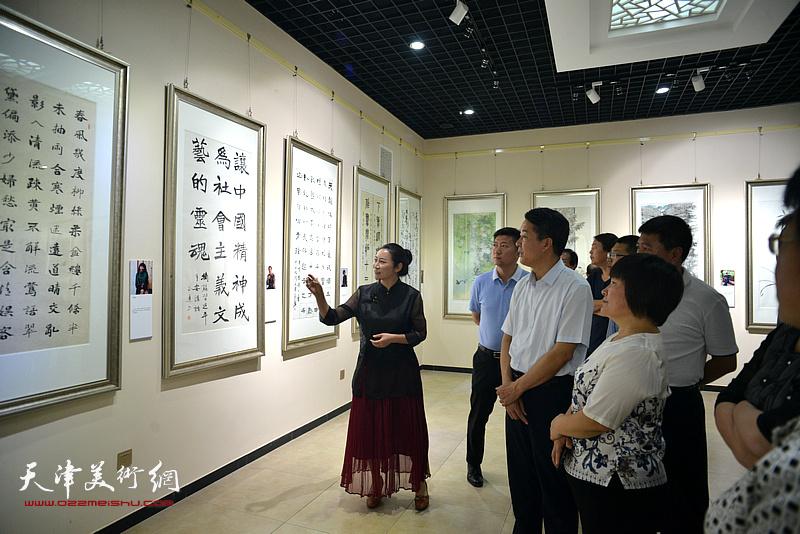赵红云向杨广才、刘亚秀等两区领导介绍展出的画作。