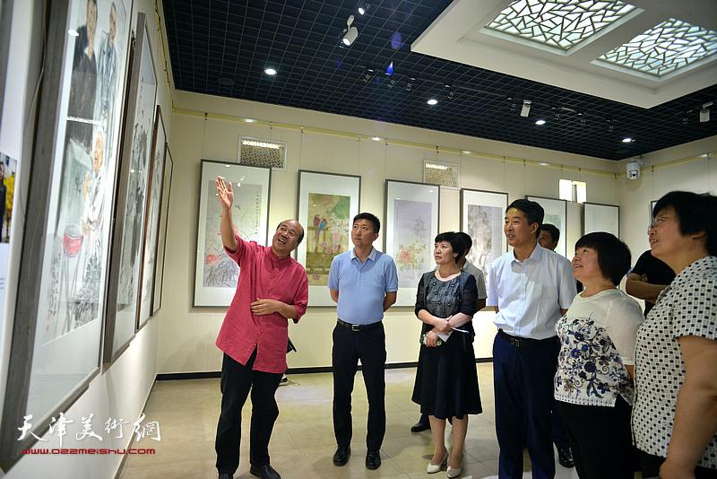孟庆占向杨广才、刘亚秀等两区领导介绍展出的画作。