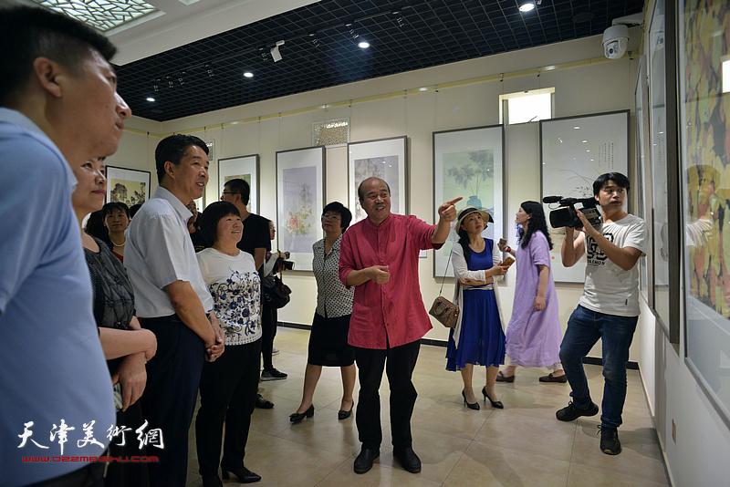 孟庆占向杨广才、刘亚秀、王栩东等两区领导介绍展出的画作。