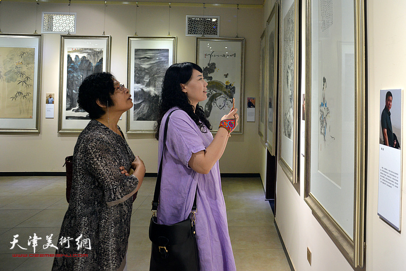 李会在观赏展出的作品。