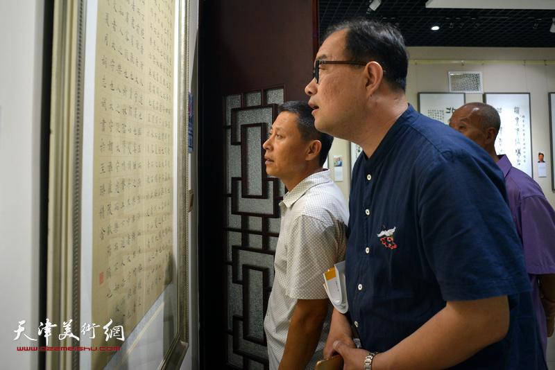 李海波、张英在观赏展出的作品。