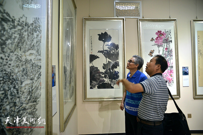 刘旭东、刘彦义在观赏展出的作品。