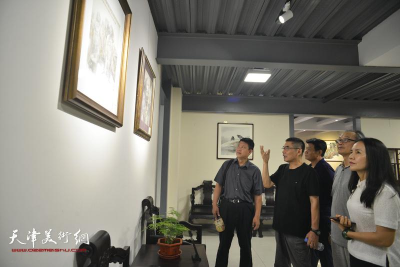 杨沛璋、陈福春与嘉宾在画展现场观赏展品。
