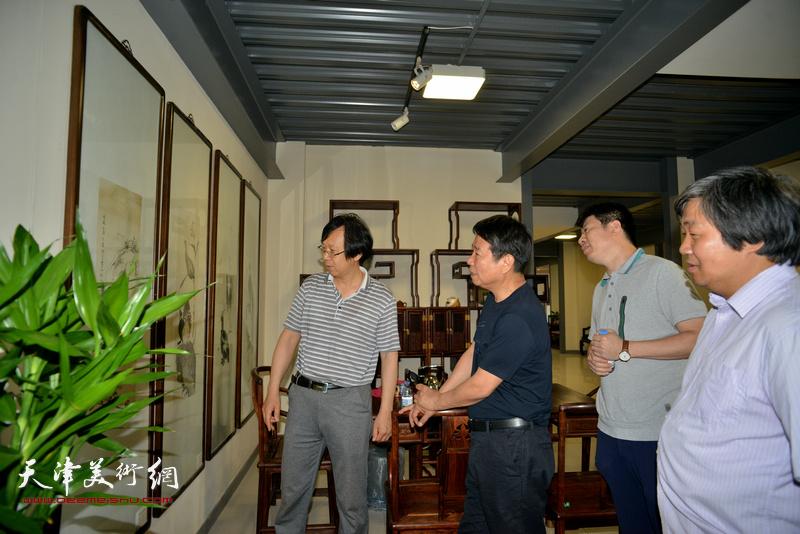 刘文生、路洪明、曾凡君、王尉在画展现场观赏展品。