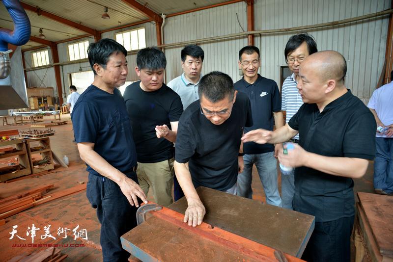 葛志强向画家们介绍家具生产工艺。