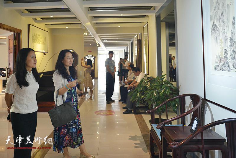 恒兴集团绿源生态园总经理张洪艳在观赏展出的作品