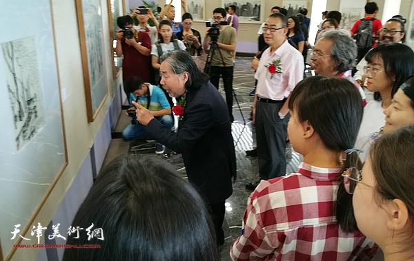 马波生陪同嘉宾观赏展出的作品。