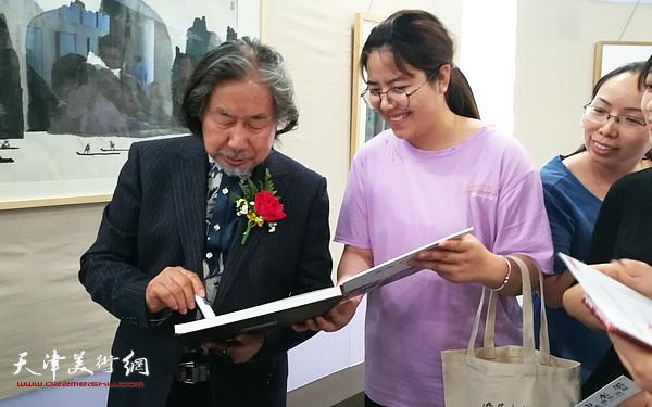 马波生在画展现场为观众签名留念。