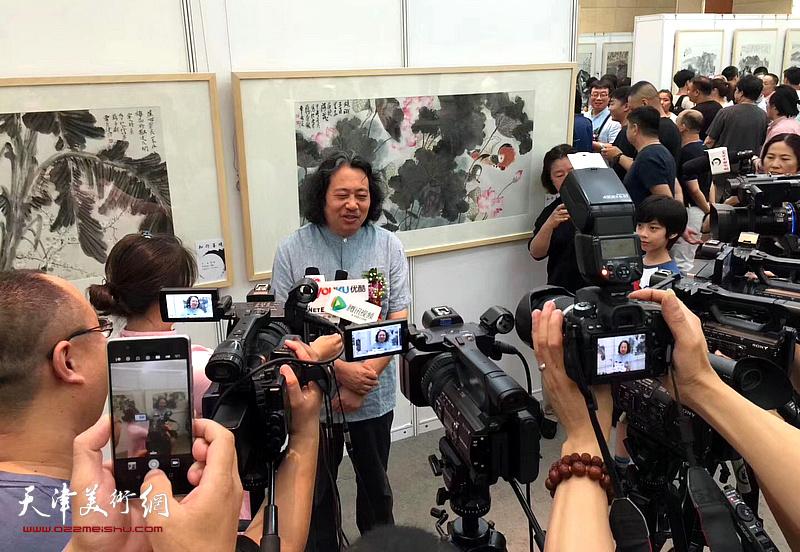贾广健在画展现场接受媒体采访