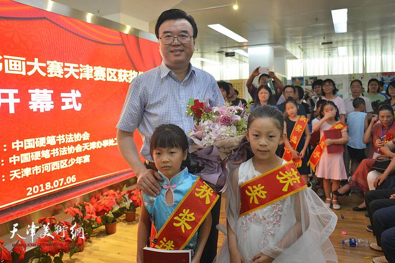 参展小画家向张华庆主席献花。