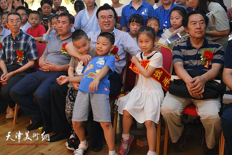 张华庆主席与参展小画家在开幕仪式上。
