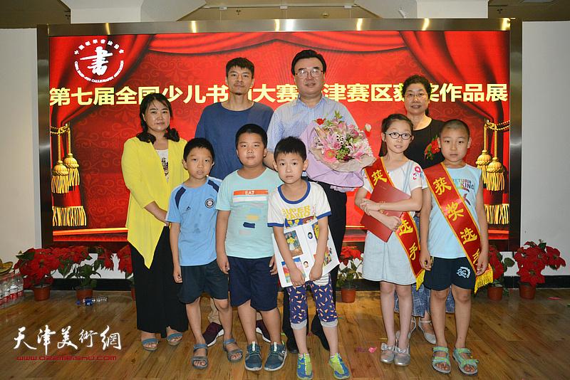 中国硬笔书法协会主席张华庆与获奖小艺术家们在画展现场。