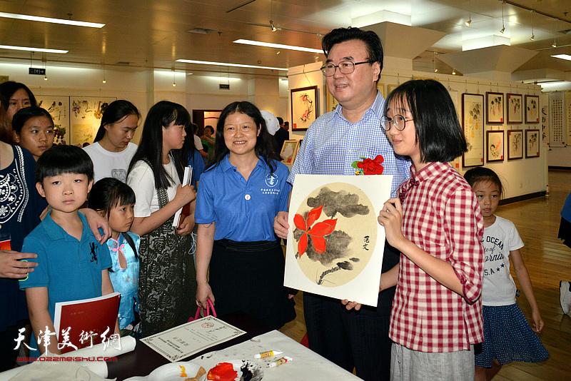 中国硬笔书法协会主席张华庆与小艺术家在画展现场。