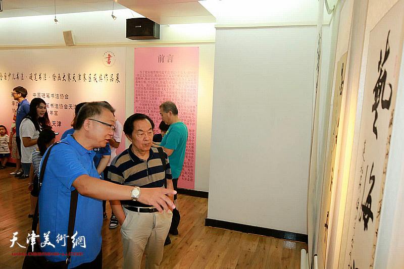 王全聚、赵炳刚观赏展出的作品。