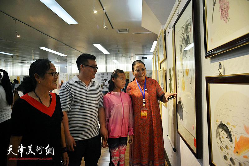 王丽荣与参展小画家及家长观赏展出的作品。