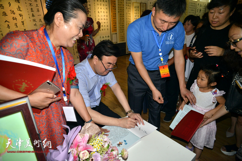 张华庆在展览现场为参展小画家签名留念。