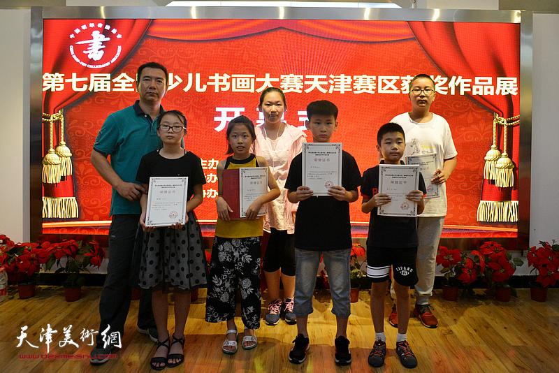 家长们与获奖小画家在展览现场。