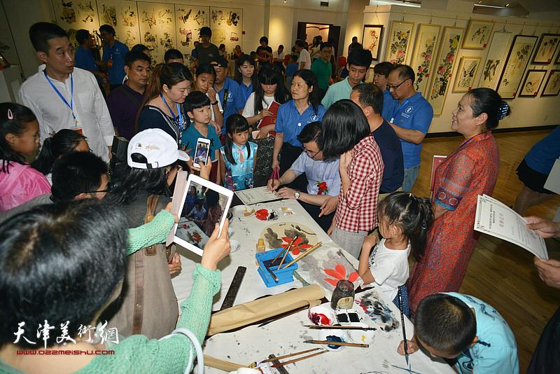 张华庆在展览现场为观众签名留念。