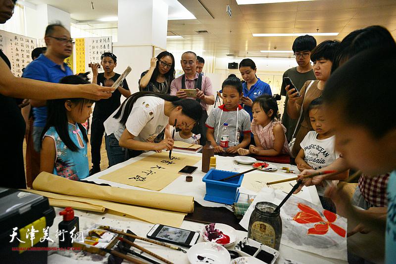 指导教师在展览现场书法书写示范。