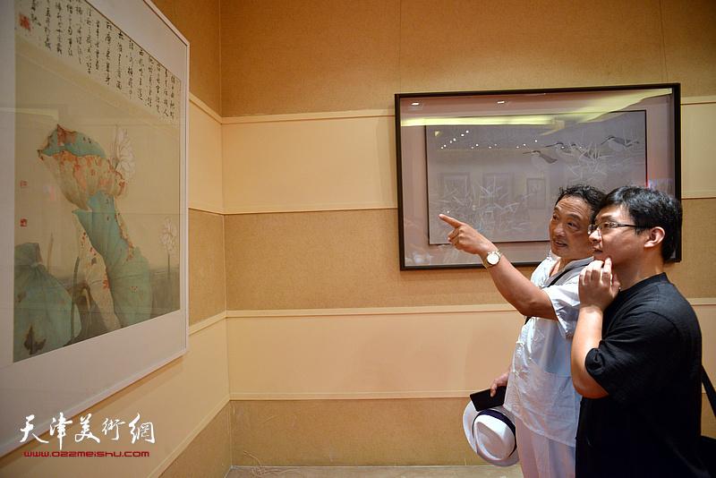 刘志君、孙文龙在欣赏展出的画作